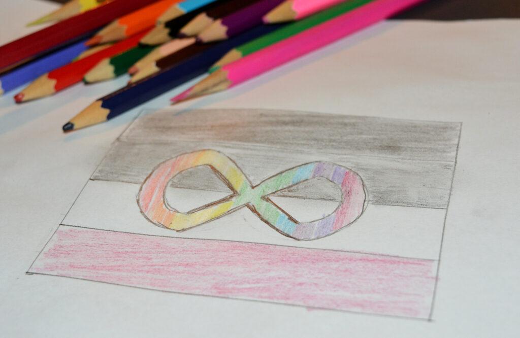 Een tekening van de aseksuele vlag met daarop een oneindigheidsteken in regenboogkleuren. Naast de vlag liggen kleurpotloden.